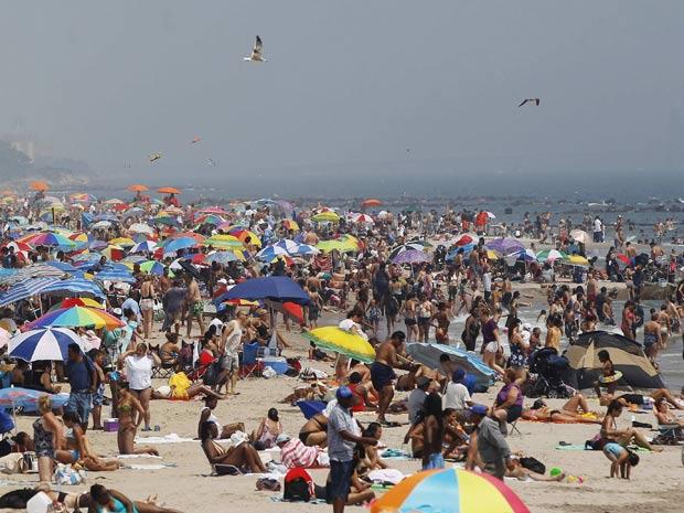 Público lota praia de Coney Islanda, em Nova York, nesta quinta-feira (21)  (Foto: Shannon Stapleton / Reuters)