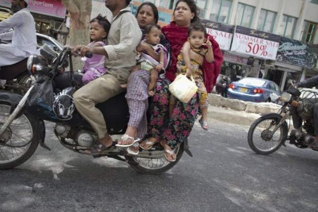 Motociclista carrega seis pessoas em moto. (Foto: Behrouz Mehri/AFP)