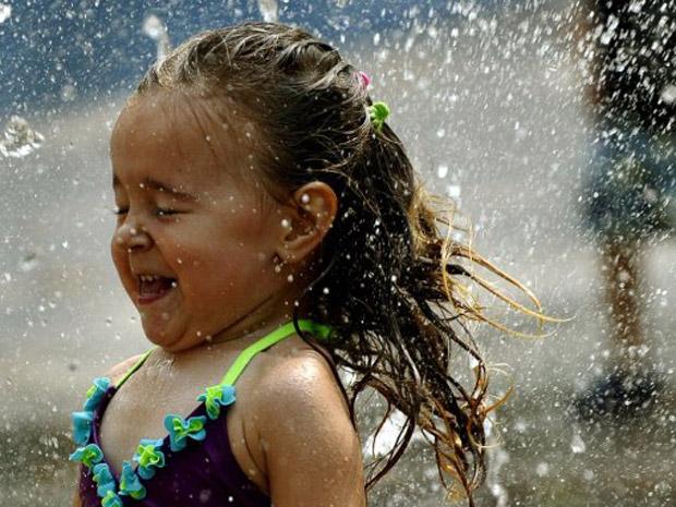 Garotinha de 3 anos refresca-se em fonte em Nova York nesta quinta-feira (21) (Foto: Reuters)