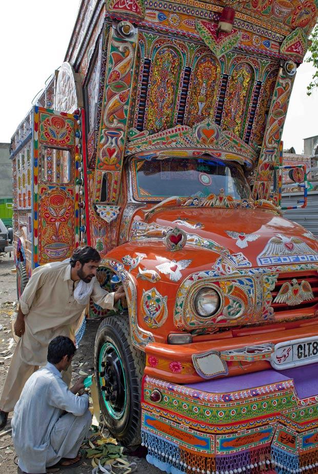 Abdul Rauf (à esquerda) observa como ficaram as pinturas de seu caminhão. (Foto: B.K.Bangash/AP)
