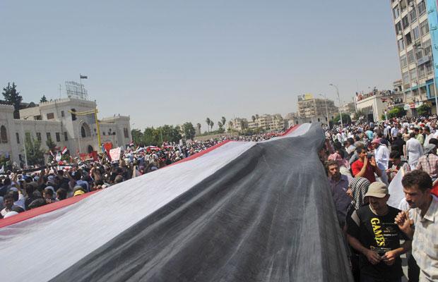 Bandeira gigante é levantada em manifestação em contra Bashar al-Assad, em Hama (Foto: Reuters)