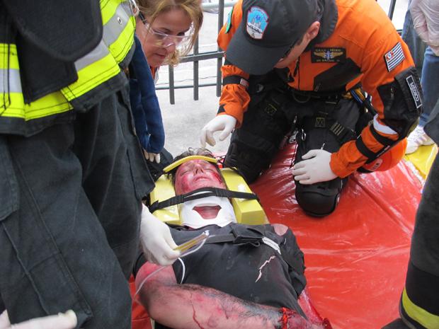 Homem é 'atendido' por bombeiros durante simulação (Foto: Letícia Macedo/G1)