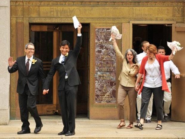 Casais homossexuais comemoram ao deixar cartório de Manhattan onde registraram união, no primeiro dia em vigor de lei no estado (Foto: Stan Honda / AFP)