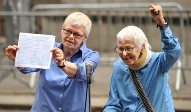 Phyllis Siegel (esq.) exibe o certificado de casamento com Connie Kopelov, que comemora após terem sido o primeiro casal a ter a união reconhecida por um cartório de Manhattan, neste domingo (24)  (Foto: Stan Honda / AFP)