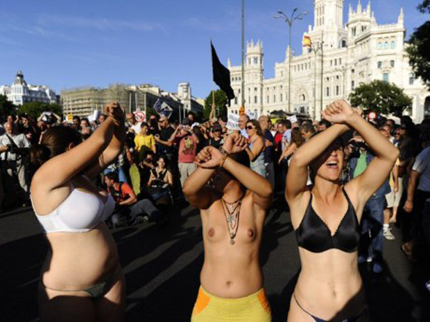 """Manifestantes nus e seminus participam do protesto dos ativistas """"indignados"""" neste domingo (23), incluindo centenas que atravessaram o país à pé, durante protesto contra o desemprego e a crise econômica (Foto: AFP)"""