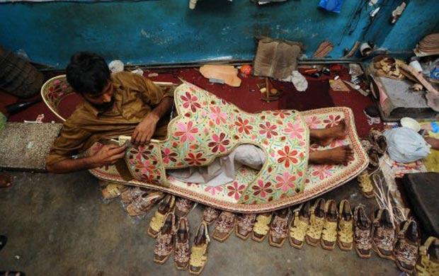 Fabricante Abdul Hameed posa dentro da sandália gigante.  (Foto: Arif Ali/AFP)