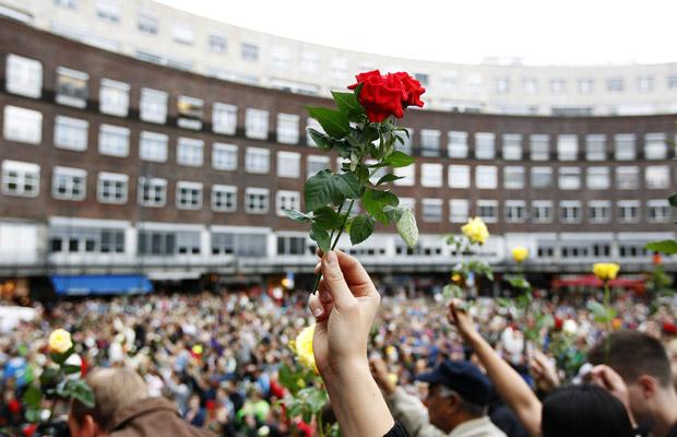 Moradores erguem rosas durante homenagem às vítimas, nesta segunda-feira (25), em Oslo (Foto: Reuters)