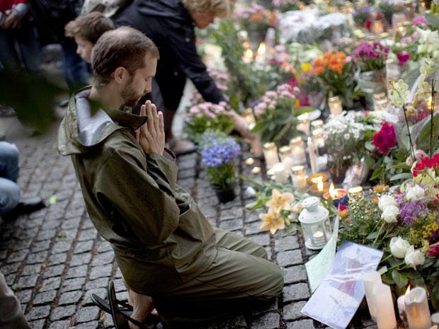 Homem faz oração em frente a flores e velas deixadas na Catedral de Oslo, no domingo (24) (Foto: Emilio Morenatti/Reuters)