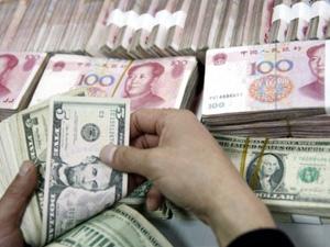 Chinês conta notas de dólar perto de notas de iuan. (Foto: AFP)