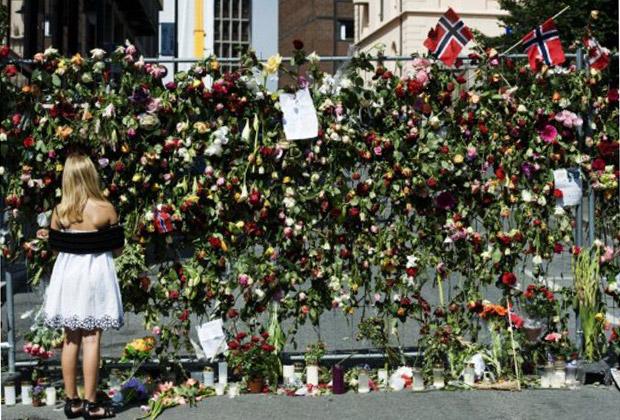 Menina observa homenagens às vítimas dos ataques, em cerca de segurança na sede do governo norueguês, em Oslo, nesta quarta-feira (27) (Foto: AFP)