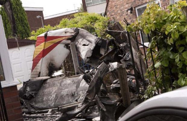 Destroços de pequeno avião que caiu entre casas na Newlands Avenue, em Salford, na Grande Manchester, nesta sexta-feira (29), provocando estragos (Foto: AFP)