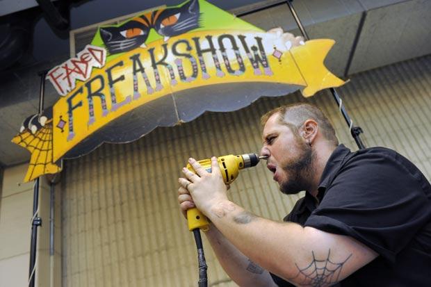 Americano Aaron Woody, de 29 anos, de Fort Collins, usa uma furradeira contra o próprio rosto durante um show de bizarrices em uma feira em Denver, no estado do Colorado (EUA), na quinta-feira (28). (Foto: Chris Schneider/AP)