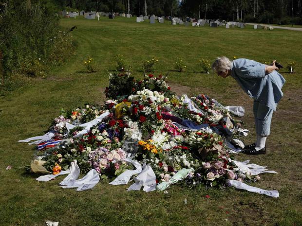 Mulher presta homenagem diante de túmulo de uma das vítimas do atirador, neste sábado (30), em cemitério em Nesodden, perto de Oslo (Foto: Reuters)
