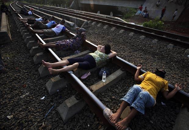 Indonésios acreditam que corrente elétrica existente nos trilhos poderia curar várias doenças. (Foto: Achmad Ibrahim/AP)