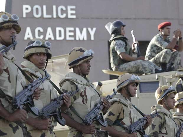Soldados do exército egípcio ajudam policiais a garantir segurança no perímetro do prédio onde Hosni Mubarak será julgado. (Foto: Amr Nabil / AP Photo)