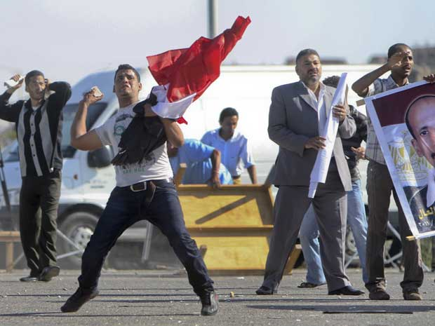 Partidários e oposicionistas de Hosni Mubarak atiram pedras antes mesmo de o julgamento do ex-líder egípcio começar. (Foto: Ahmed Ali / AP Photo)