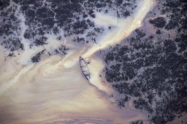 Foto tirada em março mostra água com óleo em um riacho perto de uma refinaria ilegal no Delta do Níger, na Nigéria. (Foto: AP)