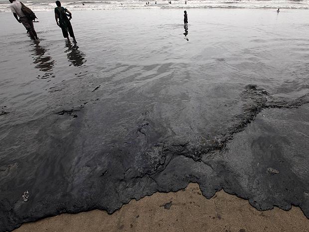 Praia de Juhu, na Índia, com óleo em sua orla (Foto: Rajanish Kakade/AP)