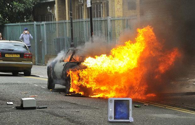 Carro em chamas é visto em rua de Hackney, Londres, nesta segunda (8) (Foto: Toby Melville/Reuters)