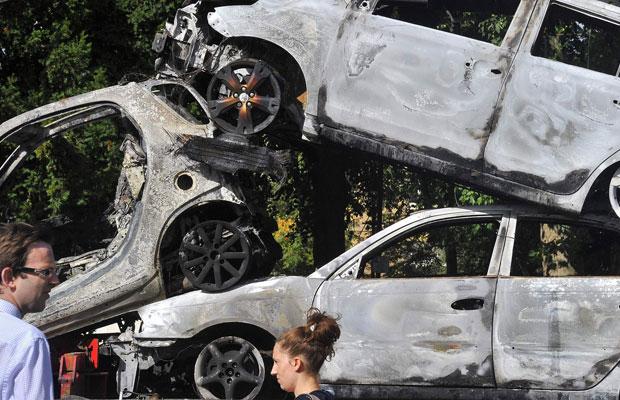 Pedestres caminham por carros queimados em Ealing, oeste de Londres, nesta terça-feira (9) (Foto: Toby Melville/Rueters)