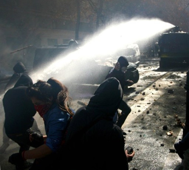 Estudantes fogem de jato d'água durante protestos em Santiago, nesta terça-feira (9) (Foto: Hector Retamal / AFP)