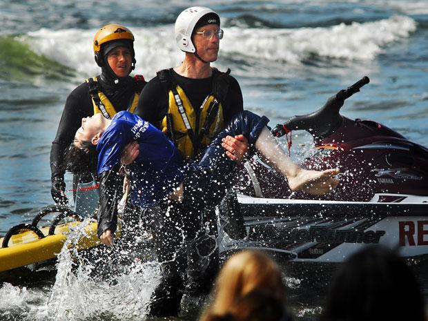 Dale Ostrander é resgatado após vários minutos desaparecido na Cranberry Beach (Foto: AP/Damian Mulinax/Chinook Observer)