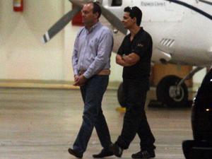 O secretário-executivo do Ministério do Turismo, Frederico Costa da Silva é conduzido algemado para avião da PF (Foto: André Dusek / Agência Estado)