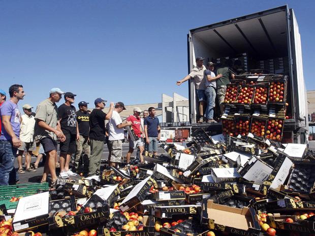 Membros do sindicato regional dos agricultores da França destruíram caixas de frutas espanholas que seriam vendidas no país. Cerca de cem agricultores franceses esvaziaram quatro caminhões carregados com frutas vindas da Espanha, vendidas a um preço menor que o produto local.  (Foto: Reuters)