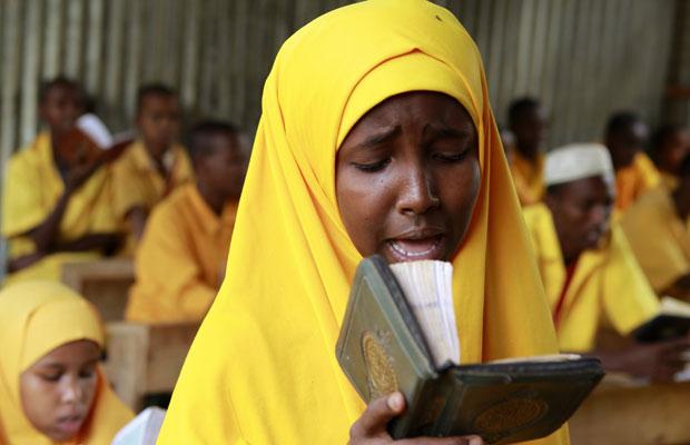Menina somali lê o Alcorão em escola islâmica de Ifo (Foto: Thomas Mukoya/Reuters)