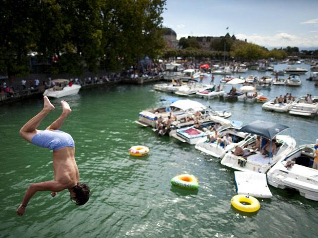Um homem pula de uma ponte na 'Street Parade', festa de música eletrônica realizada anualmente em Zurique, na Suíça. Para sua vigésima edição, realizada neste sábado (13), o evento espera receber mais de 900 mil pessoas para dançar ao som de ritmos de música eletrônica (Foto: Reuters)