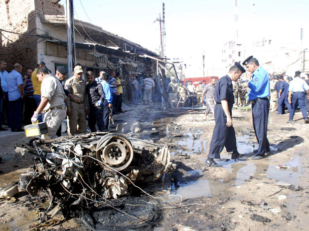 Carro-bomba destruído é visto em rua de Kut (Foto: Reuters)