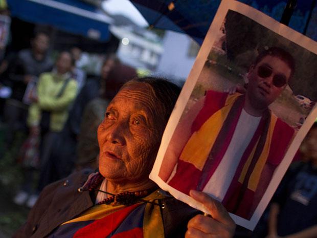 Exilada tibetana mostra uma foto de Tsewang Norbu, de 29 anos, durante vigília à luz de velas em memória ao monge suicida (Foto: Ashwini Bhatia/AP)