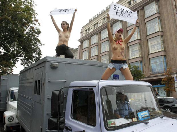 Manifestantes do grupo feminista ucraniano Femen fizeram uma manifestação com os seios à mostra nesta terça-feira (16) em Kiev. Durante o ato, as duas mulheres subiram sobre um pequeno caminhão da polícia usado para o transporte de detentos. Elas queriam chamar a atenção pública para o fato de que, na opinião do grupo, há muitos criminosos no país que precisam enfrentar a justiça, enquanto as autoridades ucranianas só têm dado atenção ao caso da líder oposicionista Yulia Tymoshenko. (Foto: Gleb Garanich/Reuters)