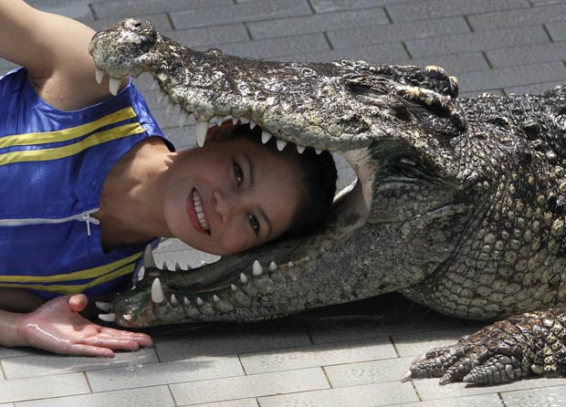 Kanthida Jantanct coloca a cabeça entre as mandíbulas de um crocodilo. (Foto: Sukree Sukplang/Reuters)