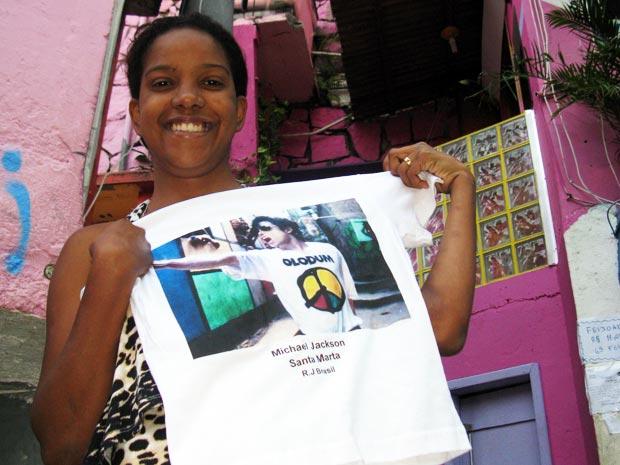 Andréia Miranda mostra uma das camisas mais vendidas, com a foto de Michael Jackson em uma das vielas da Santa Marta (Foto: Bernardo Tabak/G1)