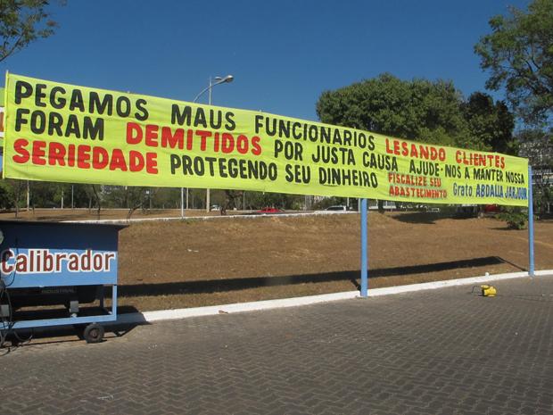 Posto do DF anuncia demissão de funcionários por justa causa em faixa. (Foto: Mariana Zoccoli/G1)
