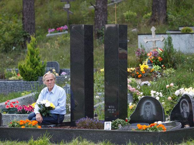 Vladimir Gavriushin coloca rosas brancas perto das réplicas de granito dos arranha-céus do World Trade Center, um memorial de 1,8 metro que ele construiu para homenagear sua filha Yelena, uma das cerca de 3.000 pessoas mortas em 11 de setembro de 2001. (Foto: AP)