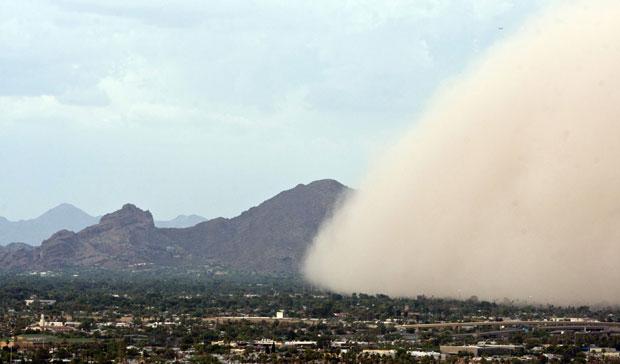 Uma nova tempestade de areia 'engoliu' cidades do Arizona nesta quinta-feira (18). É a terceira tempestade do tipo em um mês no estado americano. Acima, a montanha Camelback é vista ao fundo sento tomada pela enorme nuvem na cidade de Phoenix (Foto: AP)