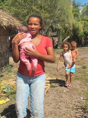 Josilda Mendes Arara com o filho caçula no colo; logo atrás, a filha mais velha de Josilda, de cinco anos, carrega a irmãzinha no colo (Foto: Mariana Oliveira / G1)