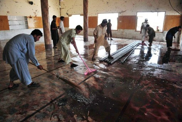 Moradores limpam sangue em mesquita alvo de explosão em Jamrud, a 25 km de Peshawar, no Paquistão (Foto: A. Majeed / AFP)