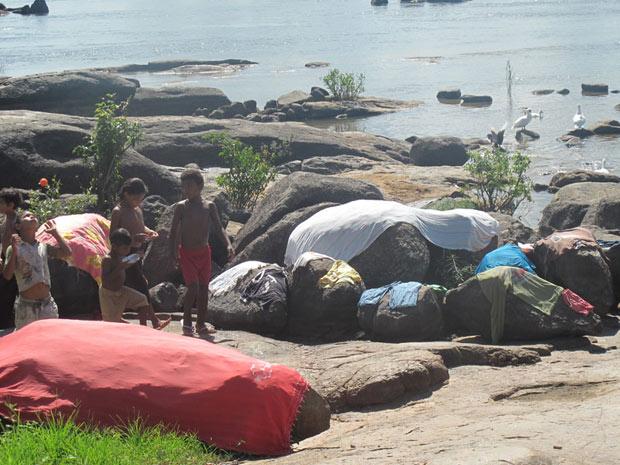 Crianças indígenas brincam na beira do rio Xingu; roupas que as índias lavam no rio secam em pedras (Foto: Mariana Oliveira / G1)