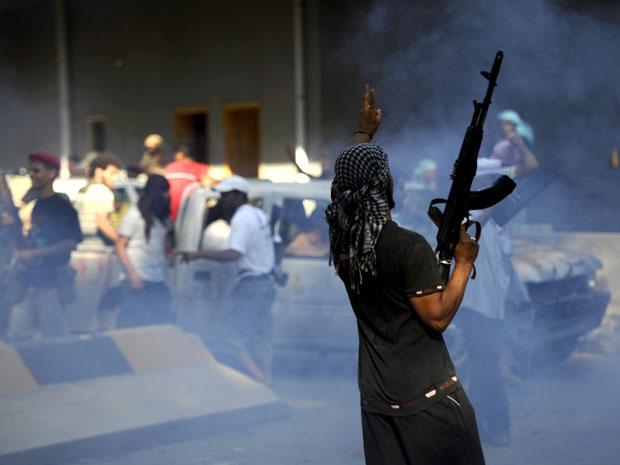 Rebelde comemora em base militar tomada a cerca de 16 km do centro de Trípoli neste domingo (21) (Foto: AFP)