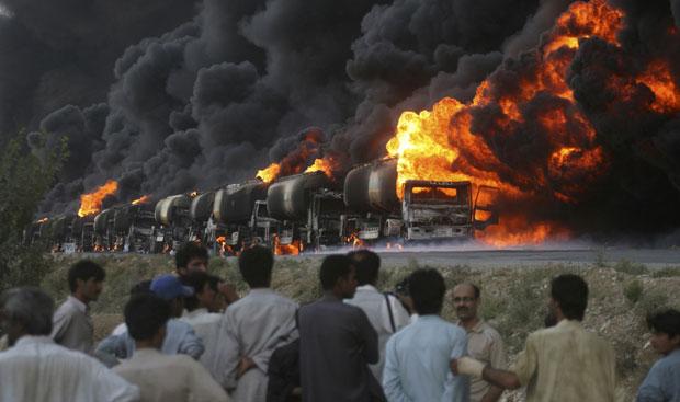 Moradores e jornalistas observam os caminhões-tanque da Otan que foram atacados e explodidos nesta segunda-feira (22) em uma via perto de Quetta, no Afeganistão. Fontes oficiais disseram que cerca de 12 homens armados pararam o comboio de 18 caminhões que levava combustível para forças da Otan no país, e os puseram em chamas. É o maior ataque do tipo registrado nas últimas semanas. Esse tipo de atentado tem sido recorrente tanto no Afeganistão quanto no Paquistão. (Foto: Naseer Ahmed/Reuters)