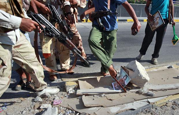 Rebeldes pisam e apontam armas para imagem do ditador em posto de controle no distrito de Qarqarsh, em Trípoli (Foto: Bob Strong/Reuters)