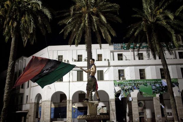Rebelde sacode bandeira da oposição a Muammar Kadhafi sobre uma fonte na Praça Verde, no centro de Trípoli, na madrugada desta segunda (22) (Foto: The New York Times)