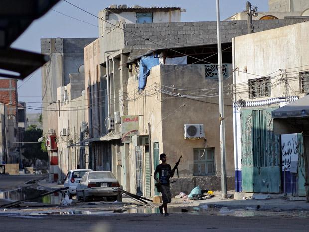 Rebelde líbio anda em rua da capital, Trípoli, nesta terça-feira (23) (Foto: AP)