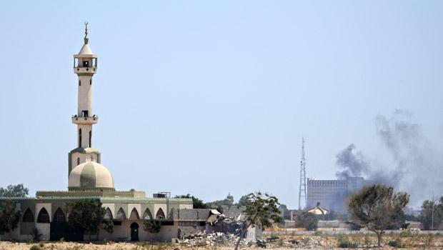 Fumaça ergue-se do complexo residencial de Kadhafi em Trípoli nesta terça-feira (23), durante o ataque rebelde (Foto: AP)