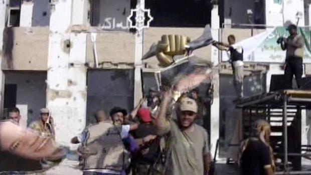 Rebeldes celebram após invadirem a fortaleza de Muammar Kadhafi em Trípoli, capital da Líbia, nesta terça-feira (23) (Foto: AP)