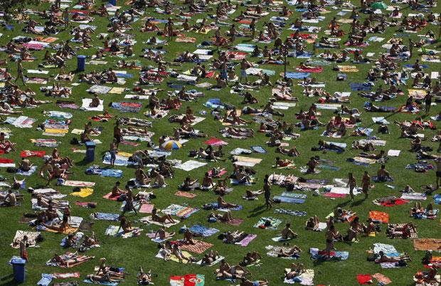 Centenas de tchecos se reuníram em Praga nesta terça-feira (23) para aproveitar o dia quente em um gramado à beira de uma piscina pública, em dia que registrou temperatura acima de 33º C. Amplie (Foto: David W Cerny/Reuters)