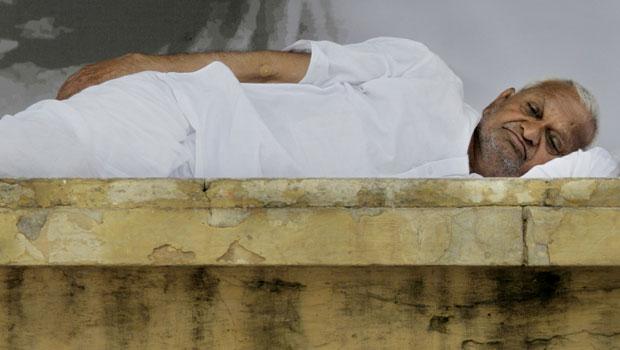 O ativista anticorrupção indiano Anna Hazare descansa nesta quarta-feira (24), no novo dia de sua greve de fome, em Nova Délhi. O governo da Índia convocou todos os partidos do Parlamento para discutir as demandas do ativista e debater  a legislação contr (Foto: AP)